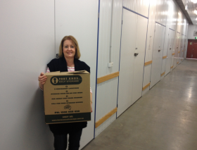 Customer Jackie carrying Fort Knox Moving Box into Storage Unit