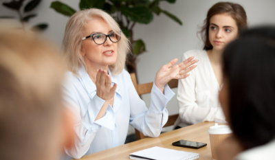 Woman talking to a group of people at a boardroom table