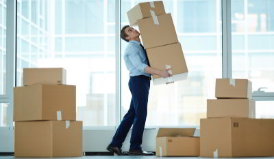 Business man moving boxes around a room