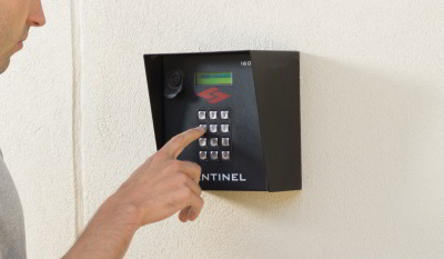 person entering PIN on Sentinel keypad at Fort Knox Self Storage entrance